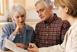 An elder care professional counsels a senior couple